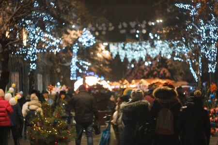 공, 장난감, 램프 및 화환으로 밤 거리에 장식된 크리스마스 트리 스톡 콘텐츠