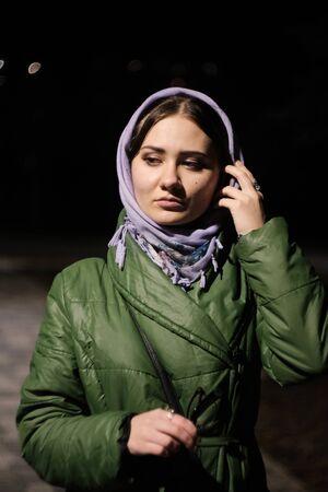Beautiful young woman in a purple traditional Russian shawl at winter night Фото со стока