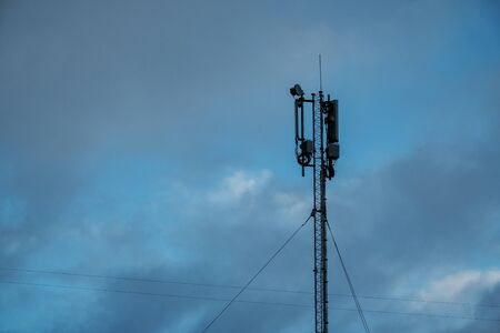 Telecommunication tower with antennas with cloudy blue sky 版權商用圖片