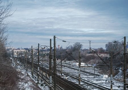 Detail of overhead lines and industrial railway landscape in train station, with platforms, electric pylons and railroad switches turnouts on the tracks Imagens