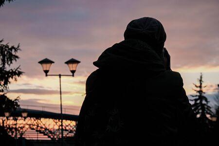 Man silhouette at row of illuminated lanterns in the evening bridge