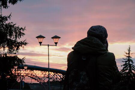 Man silhouette at row of illuminated lanterns in the evening bridge 版權商用圖片 - 148162719