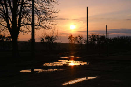 Sunset cloudy landscape after the rain over abandoned soccer field with puddles Zdjęcie Seryjne