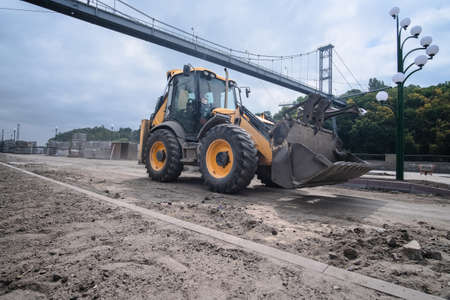 Excavator at reconstruction coastal structures, construction of quay at small town