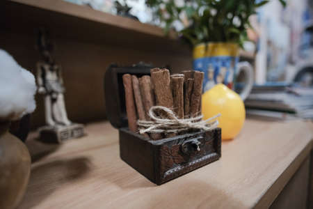 Cinnamon pods in wooden treasure box on the table.