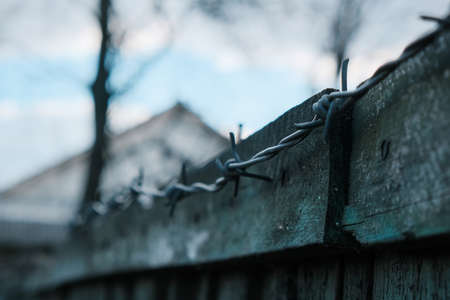 Barbed wire under electricity above the fence.