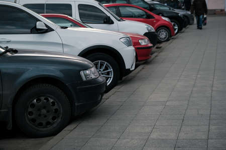 Cars at parking lot in row near the road