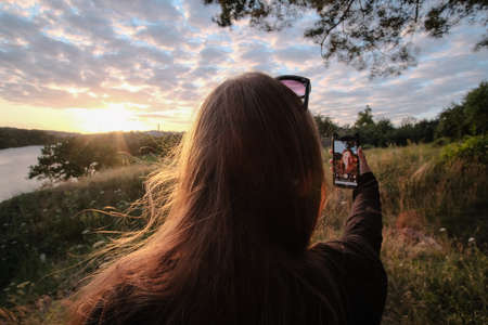 Young happy woman making selfie in the sun, in a sunset summer forest. Zdjęcie Seryjne
