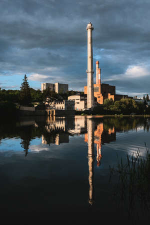 The old factory with smoking chimneys on the banks of the river. Vertical view