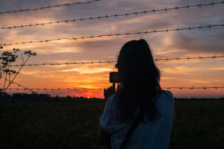 Girl shooting on phone orange hanging curtains of smoke from a large wildfire and obscuring a firefighting plane in the sky at fence background.