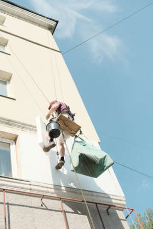 Thermal insulation of the exterior wall panel. Worker man insulates wall high-rise building. Zdjęcie Seryjne
