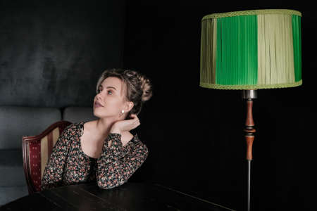 beautiful thoughtful woman sitting at dark room with green table lamp
