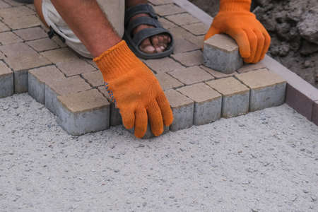 Construction worker installing and laying pavement stones on terrace, road or sidewalk. Worker using stones to build sidewalk