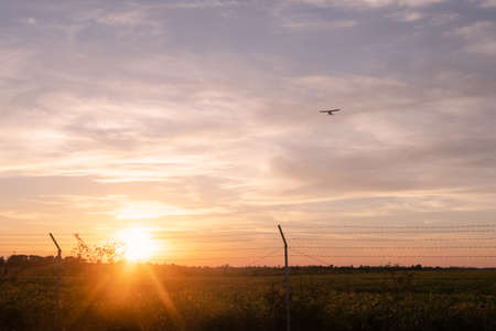 A jet approach landing with a barbed wire fence in the foreground. At evening sky background Foto de archivo