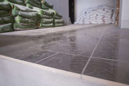 Spot focus on the floor at the construction site during installation of floor tiles