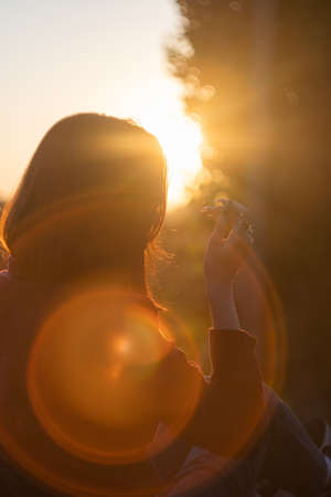 Silhouette portrait of young serious woman. Silhouette of a young woman relaxing on a beautiful sunset. Happy woman enjoying nature sunset. Freedom, happiness, enjoyment, concept of beautiful girl. Foto de archivo