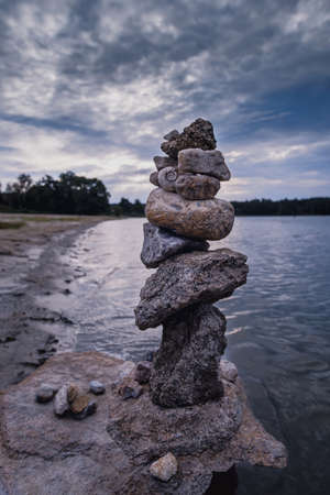Stone arrange in balance in the bank of the river with dramatic cloudy sky. Vertical view