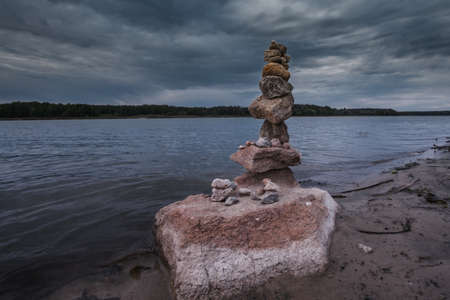 Stone arrange in balance in the bank of the river with dramatic cloudy sky. Foto de archivo
