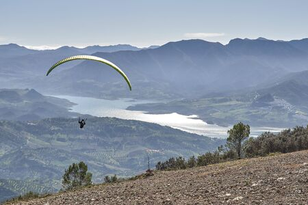 man doing paragliding in Lija Cadiz with blue sky and lake at the background