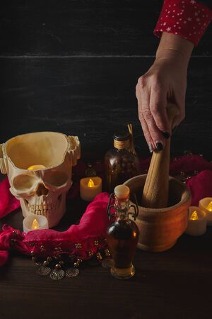 Hand using mortar Scary still life with potions, skull, mortar, vintage bottles and candles on witch table. Halloween or esoteric concept. Black magic and occult objects in evil interior