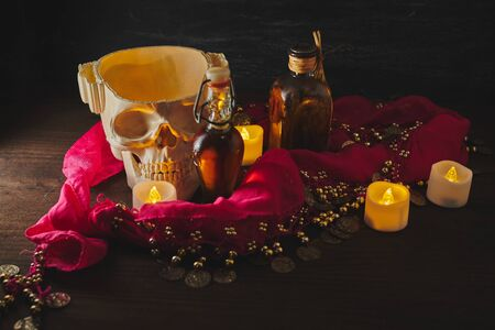 Scary still life with potions, skull, mortar, vintage bottles and candles on witch table. Halloween or esoteric concept. Black magic and occult objects in evil interior