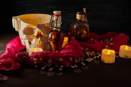 Bodegón aterrador con pociones, calavera, mortero, botellas vintage y velas en la mesa de brujas. Halloween o concepto esotérico. Magia negra y objetos ocultos en el interior del mal.