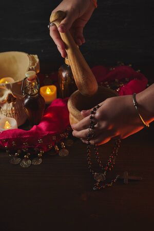 Hand using mortar Scary still life with potions, skull, mortar, vintage bottles and candles on witch table. Halloween or esoteric concept. Black magic and occult objects in evil interior Banque d'images