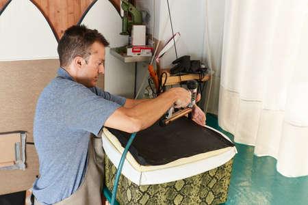 Qualified workman upholstering furniture in repair furniture workshop