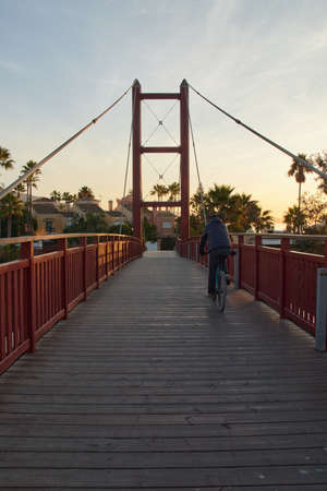 Rear view of man riding bicycle on bridge in city over a wood bridge at the sunrise