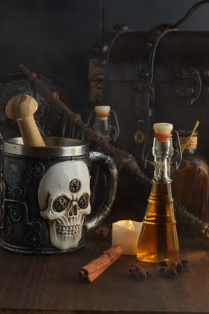 Magic potions in bottles, coffer and Magic wand on dark wooden background