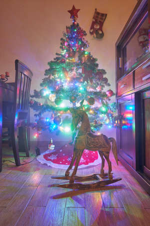 Christmas decoration in grunge room interior, horse rocking kids chair, classic new year tree