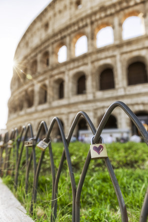 Red heart on a padlock in front of the Colosseum in Rome, Italy