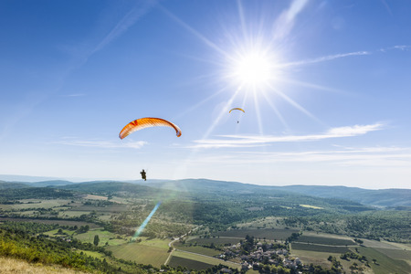 high flier: Two paragliders under the rays of a white sun