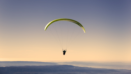 parachute jump: Yellow paragliding on pastel  sky