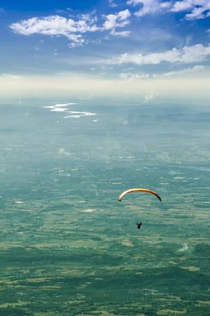 high flier: Orange glider overlooking the Rhone under a cloudy sky