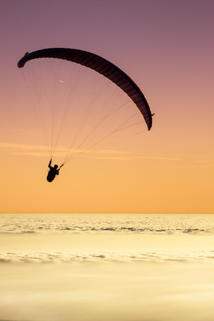 Paragliding above a sea of clouds with a pastel sky