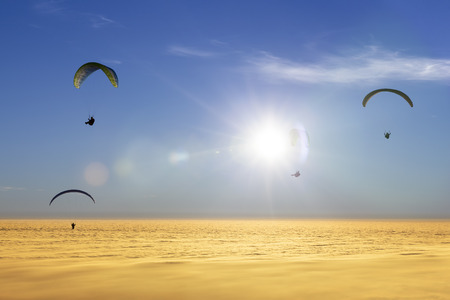 Four paragliders over a sea of clouds with sun Stock Photo