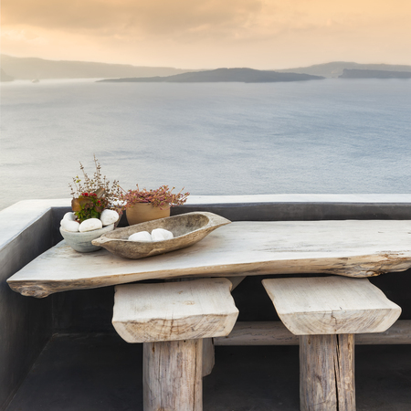 Wooden table and stools on a terrace in Santorini Stock Photo