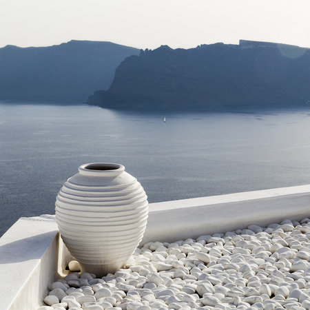 White vase with pebbles on rooftop in Santorini