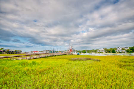 Shrimp boats in the distance across a salt-marsh with a boardwalk to get to them on Shem creek in Mount Pleasant, South Carolina near Charleston. Imagens