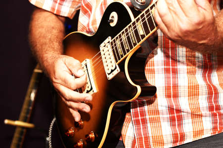 A close up of a man playing guitar. 写真素材