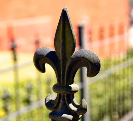A cast iron fleur-de-lis on top of a fence post. Stock fotó