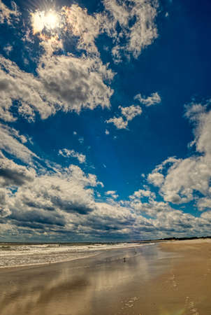 A wide angle view of a beautiful sandy beach with a lovely blue cloudy sky above at Pawleys Island, South Carolina, USA. Stock fotó