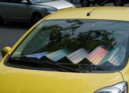 the sun and shade: The car with sun shade on the windshield in a parking lot. Folding holographic Sunshade. Stock Photo