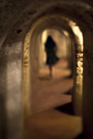 Woman walking alone down a tunnel in Cartagena, Colombia Standard-Bild