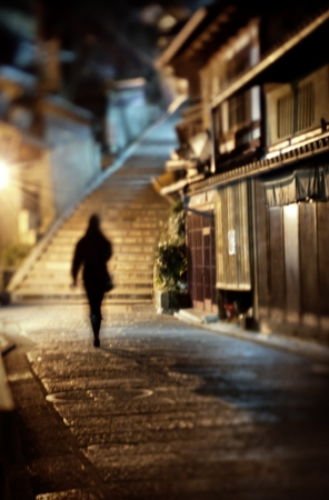 sad lonely girl: Woman walking alone along a cobblestone road at night in Kyoto, Japan Stock Photo
