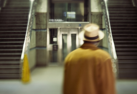 Man walking passed stairs in Union Station, train station, in Los Angeles, California