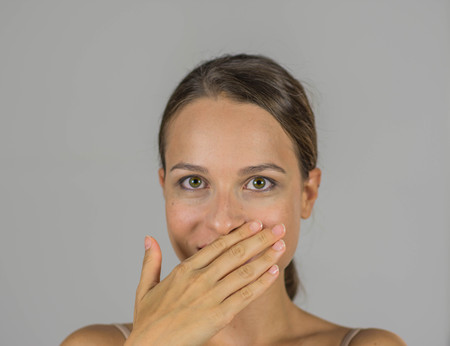 halitosis: Beautiful girl with hand on her mouth