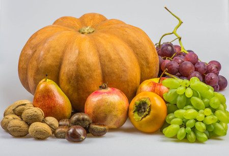 peer to peer: Still life, autumn food on white background - Pumpkin, chestnuts, walnuts, persimmon, peer, apple, pomegranate, grapes