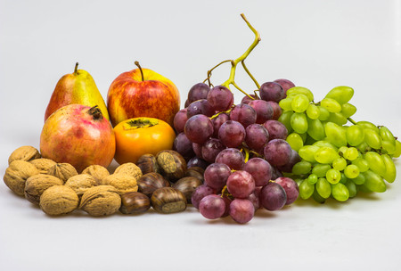 peer to peer: Still life, autumn food on white background - Chestnuts, walnuts, persimmon, peer, apple, pomegranate, grapes